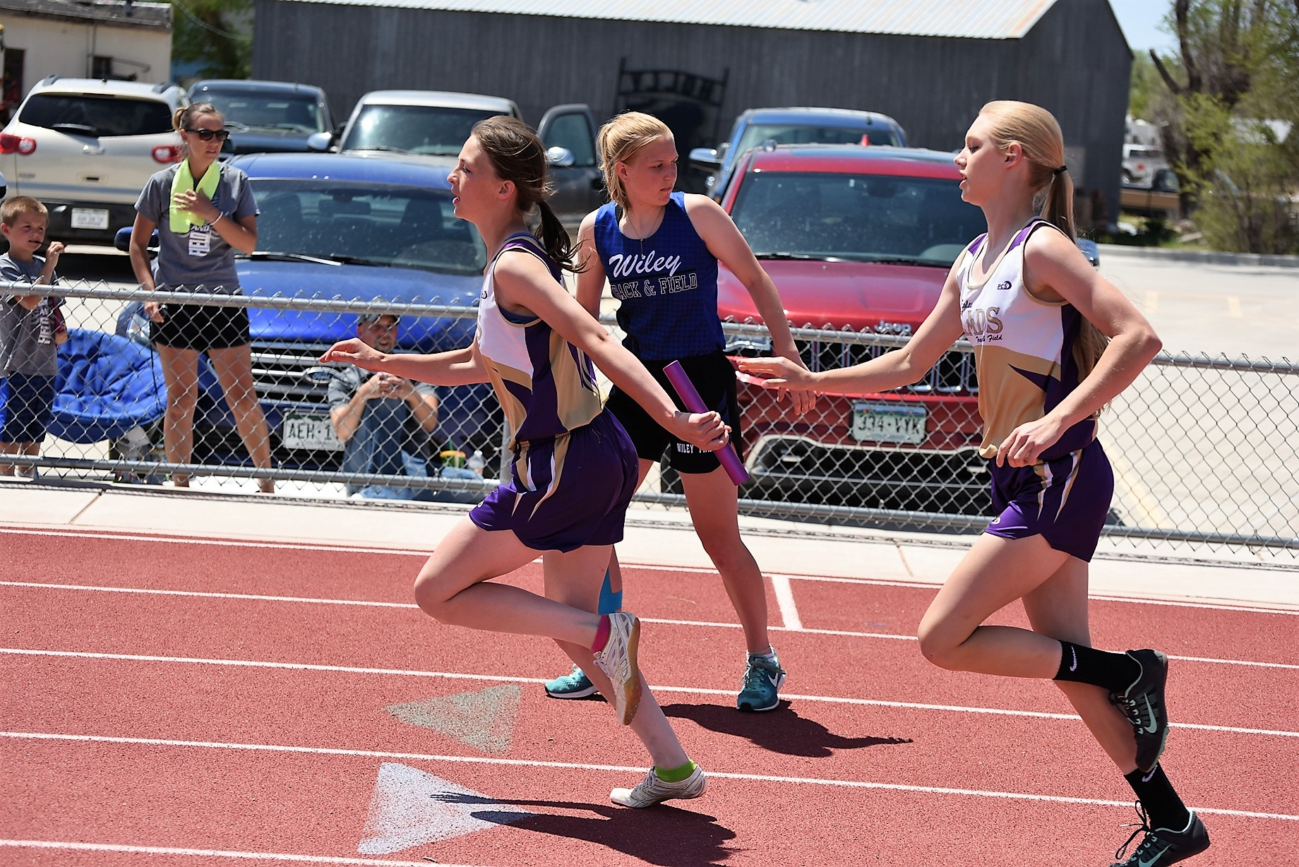 Kaycee Ellenberger (200M leg) hands off to anchor Reagen Johnson (400M leg) in the school record breaking 800M Sprint Medley Relay.  (Photo credit: WildctPridePhoto.com)