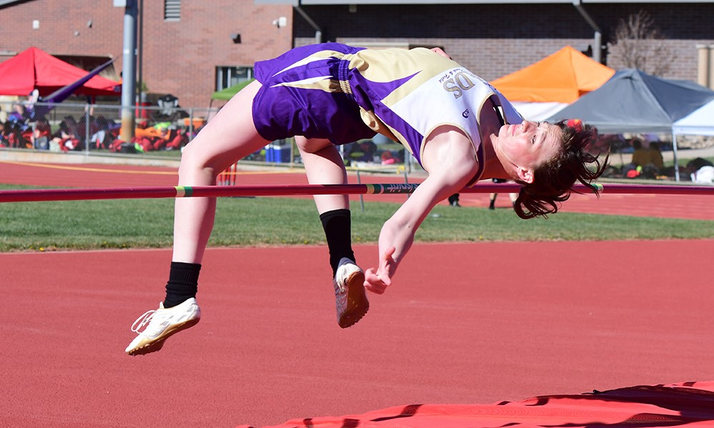 Reagen Johnson clears the bar in the girls high jump at Holly - John Schecter