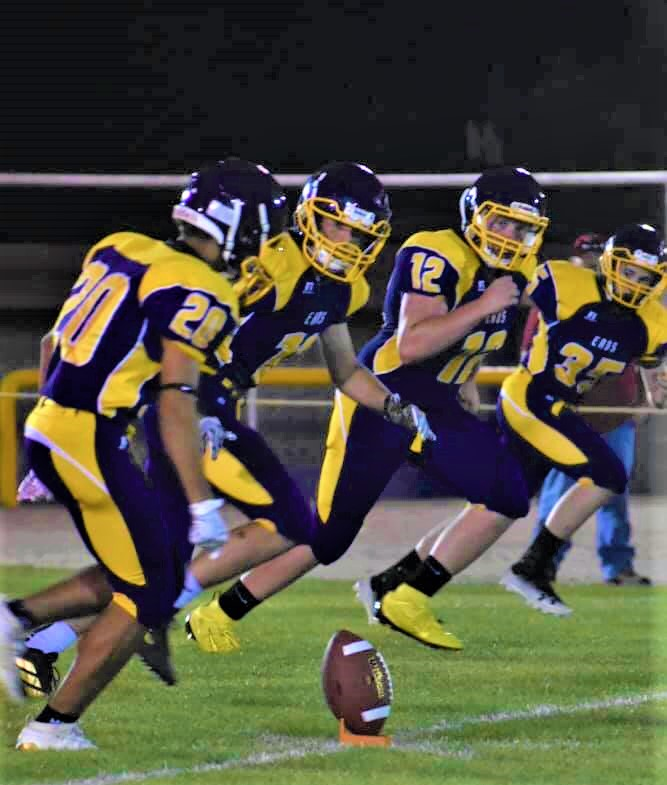 Donte Sierra (#20) attempts the squid kick while teammates Ty Wilson (#11), Cade McDowell (#12), and Hatch Nelson (#35) prepare to chase down the offense. - Photo Credit Sharon Wilson
