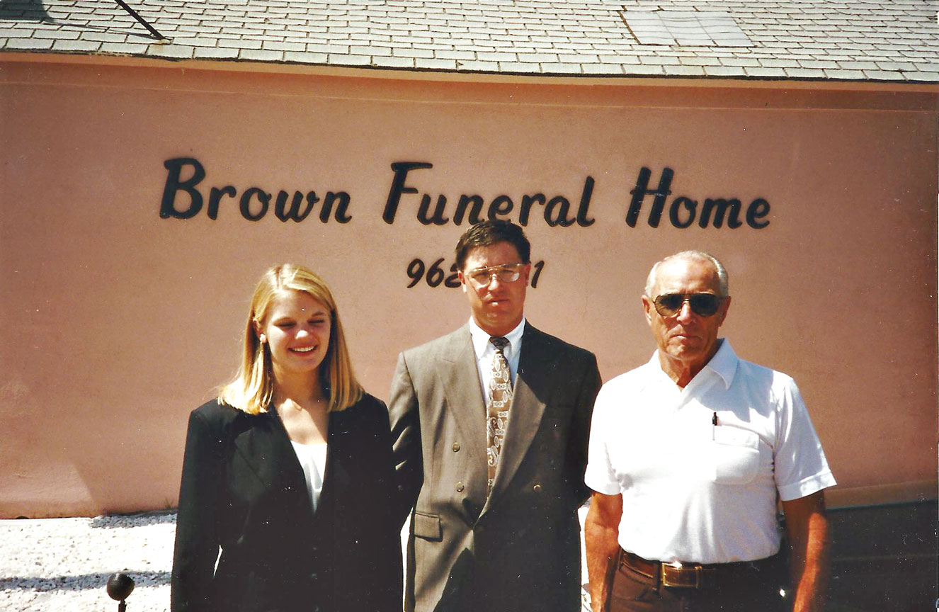 Amanda and Jimmy Brown with Wayne Singer in front of the Kit Carson Brown Funeral Home